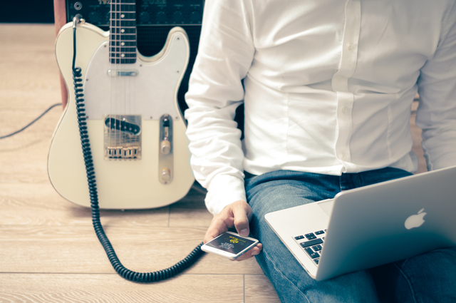 Man with guitar & Apple devices