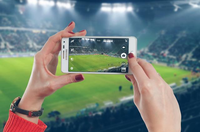 Woman uses mobile on the football stadium